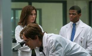 Peter Jahrling (Topher Grace), un virologiste civil, regarde à travers l'oculaire du microscope avec le Dr Nancy Jaax (Julianna Margulies) et Ben Gellis (Paul James) dans «The Hot Zone».