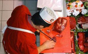Un boucher découpe une piéce de boeuf au rayon boucherie d'un Intermarché, de Chalonnes-sur-Loire, en décembre 2004