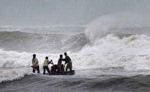 Des pêcheurs indiens tentent de sortir leur barque des fortes vagues le 11 octobre 2014 à Visakhapatnam alors que le cyclone Hudhud arrive sur les côtes de l'Inde