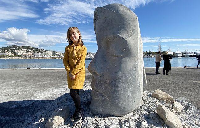 Anouk, 9 ans, pose à côté de son double de ciment