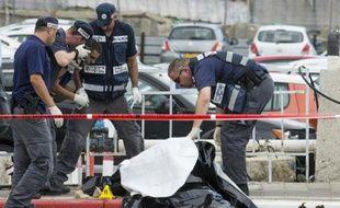 Les forces de sécurité israéliennes inspectent le corps d'un Palestinien abattu après avoir agressé au couteau une soldate israélienne et trois passants dans la ville côtière de Tel Aviv, en Israël, le 8 octobre 2015