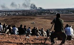 Des Kurdes regardent la fumée au-dessus de la ville de Kobané lors de frappes aériennes de la coalition, depuis une colline à Mursitpinar, le 15 octobre 2014, à la frontière syro-turque