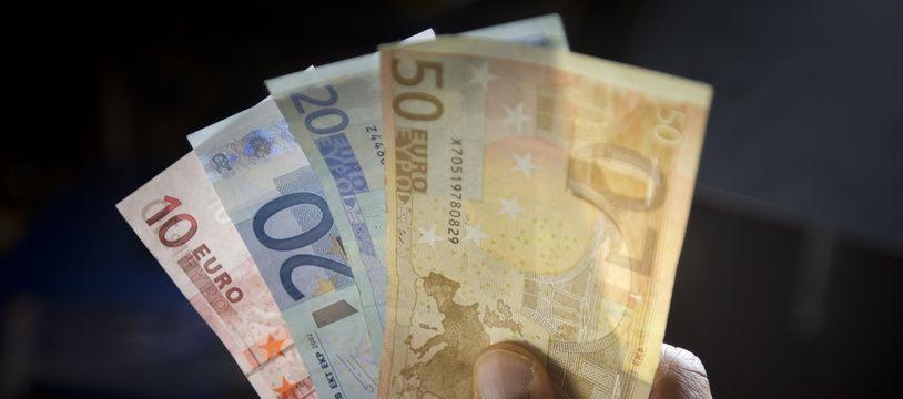 Paris le 04 fevrier 2013. Illustration  argent, billets de banque tenus dans une main.