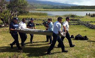 Des policiers transportent le débris appartenant peut-être à l'avion MH370 retrouvé sur une plage de Saint-André, à la Réunion, le 29 juillet 2015.