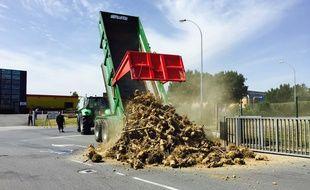 Un tracteur déverse des déchets pour bloquer l'entrée du site.