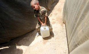 Un petit irakien dont la famille a fui Ramadi, porte un jerrican d'eau dans un camps de réfugiés, le 18 mai 2015 à Bzeibez à la frontière de Bagdad et Anbar