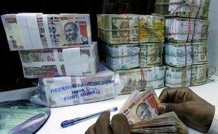 Un employé de banque compte des roupies, à Bombay le 27 février 2007