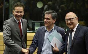 Euclide Tsakalotos, entre le ministre hollandais des Finances et président de l'Eurogroupe Jeroen Dijsselbloem et son homologue français Michel Sapin, le 7 juillet lors d'une réunion de l'Eurogroupe à Bruxelles.