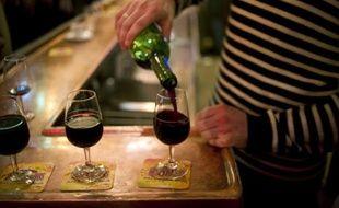 Un serveur remplit des verres de vin rouge sur le comptoir d'un bar de Paris, le 2 décembre 2011.