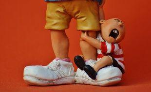 Figurine d'un enfant pleurant accroché aux pieds de sa baby-sitter. Illustration.