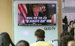 """Des Sud-coréens regardent le président américain Donoald Trump à la télévision, le 9 août 2017 à Séoul. La Corée du Nord a averti ce jour-là qu'elle pourrait tirer des missiles près de l'île américaine de Guam, alors que Donald Trump a promis au régime nord-coréen """"le feu et la colère"""" ."""