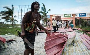Une femme ramasse des débris métalliques suite au passage du cyclone Idai, à Beira, au Mozambique