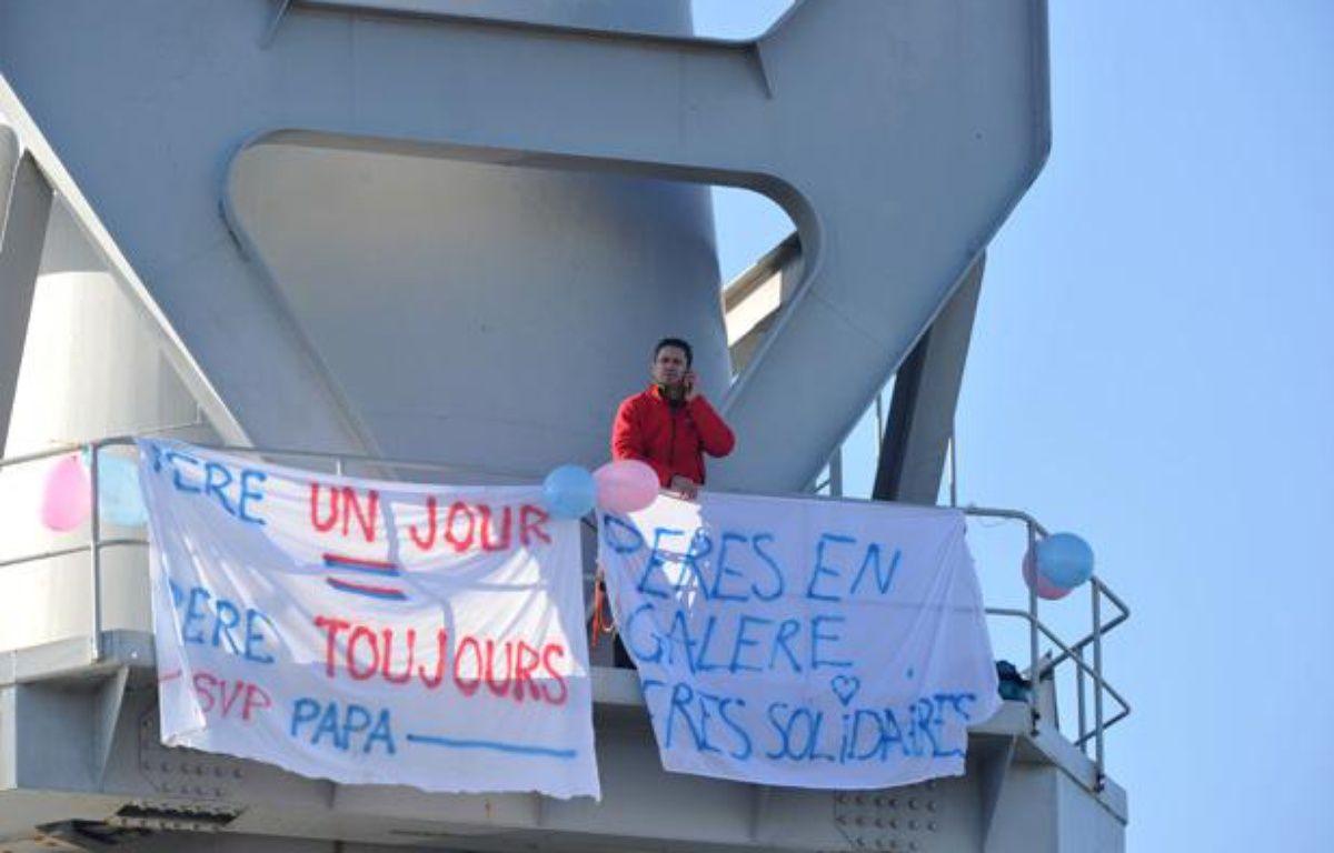 Nicolas Moreno, membre de l'association «SVPPapa», est retranché dans une grue Titan sur les chantiers navals de Nantes, le 16 février 2013. – AFP PHOTO / FRANK PERRY