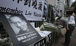 Hong-Kong, le 14 juillet 2017. Une femme rend hommage à Liu Xiaobo, prix Nobel de la paix en 2010, après sa mort.