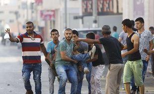 Des Palestiniens portent un homme bléssé après un raid israélien