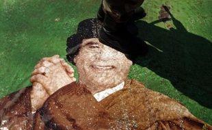 Un rebelle libyen marche sur un portrait de Mouammar Khadafi, le 22juin 2011 à Benghazi.
