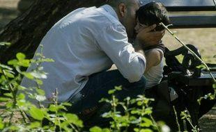 Un père conforte son fils alors qu'ils cherchent à pénétrer en Hongrie depuis la ville serbe de Kanjiza en Serbie, le 2 août 2015