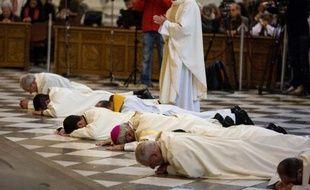 L'archevêque de Grenade, Mgr Francisco Javier Martinez (3e à d), se prosterne lors d'une messe avec d'autres religieux dans la cathédrale de la ville le 23 novembre 2014, en signe d'excuse envers les victimes d'abus sexuels de la part de prêtres