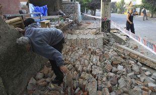 Un homme range les décombres de sa maison, à Santiago du Chili, la capitale, après un violent séisme qui a touché le nord du pays.