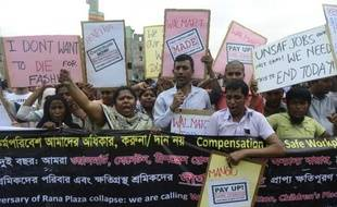 Des Bangalais du syndicat des travailleurs du textile manifestent, avec des survivants du Rana Plaza, pour réclamer le renforcement de leurs droits et de leur sécurité, le 24 avril 2015 à Savir, près de Dhaka, deux ans après la catastrophe