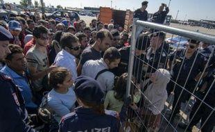 Des policiers autrichiens encadrent des migrants et des réfugiés qui attendent de monter dans des bus, le 12 septembre 2015 près de Nickelsdorf, à la frontière avec la Hongrie