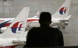 Un homme regarde des avions de Malaysia Airlines à l'aéroport de Kuala Lumpur, en Malaisie, le 27 mai 2014.