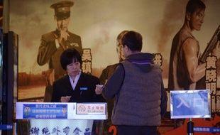 Un membre du personnel de la Maison du cinéma à Pékinvérifie le billet d'un client le 10 Janvier 2013