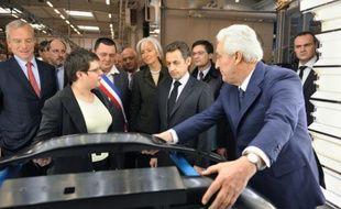 Le PDG de Plastic Omnium Laurent Burell (d) aux côtés de Nicolas Sarkozy, alors président de la République, lors d'une visite de son usine de Sainte-Julie, dans l'Aveyron, le 26 février 2009