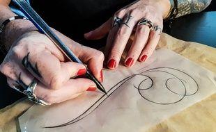 Laureen, tatoueuse, prépare le dessin pour une cliente atteinte d'un cancer du sein.