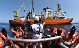 Des migrants s'apprêtent à monter à bord de  l'Aquarius, navire affrété par SOS Méditerranée et Médecins sans frontières (MSF) lors d'une opération de sauvetage le 24 mai 2016 en Méditerranée au large de la Libye