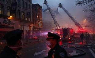 Des policiers new-yorkais devant les lieux d'un incendie avec en arrière plan les pompiers qui luttent pour circonscrire un incendie à New York le 26 mars 2015