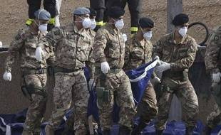 Des militaires italiens transportent le corps d'un immigré décédé dans un naufrage au large de l'île de Lampedusa, le 6 octobre 2013.
