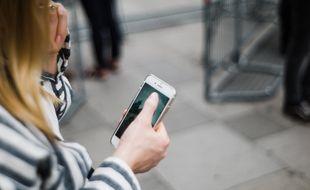 Une femme marchant dans la rue en utilisant son smartphone (illustration).