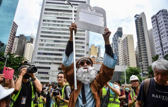 A man dressed as 'Moses' shows a placard with the 'Five Commandments' referring to anti-government protesters' demands during a protest at Southorn Playground in Hong Kong on August 31, 2019. - Thousands of pro-democracy protesters defied a police ban on rallying in Hong Kong on August 31, a day after several leading activists and lawmakers were arrested in a sweeping crackdown. (Photo by Lillian SUWANRUMPHA / AFP)