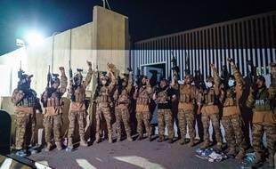 A l'aéroport de Kaboul, des combattants talibans brandissent des armes, de l'équipement et des uniformes américains peu après le départ des Etats-Unis, le 31 août 2021.