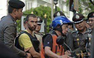 Un suspect de l'attentat du 17 août 2015 assis sur une moto-taxi prend part à une reconstitution de l'attentat le 26 septembre 2015