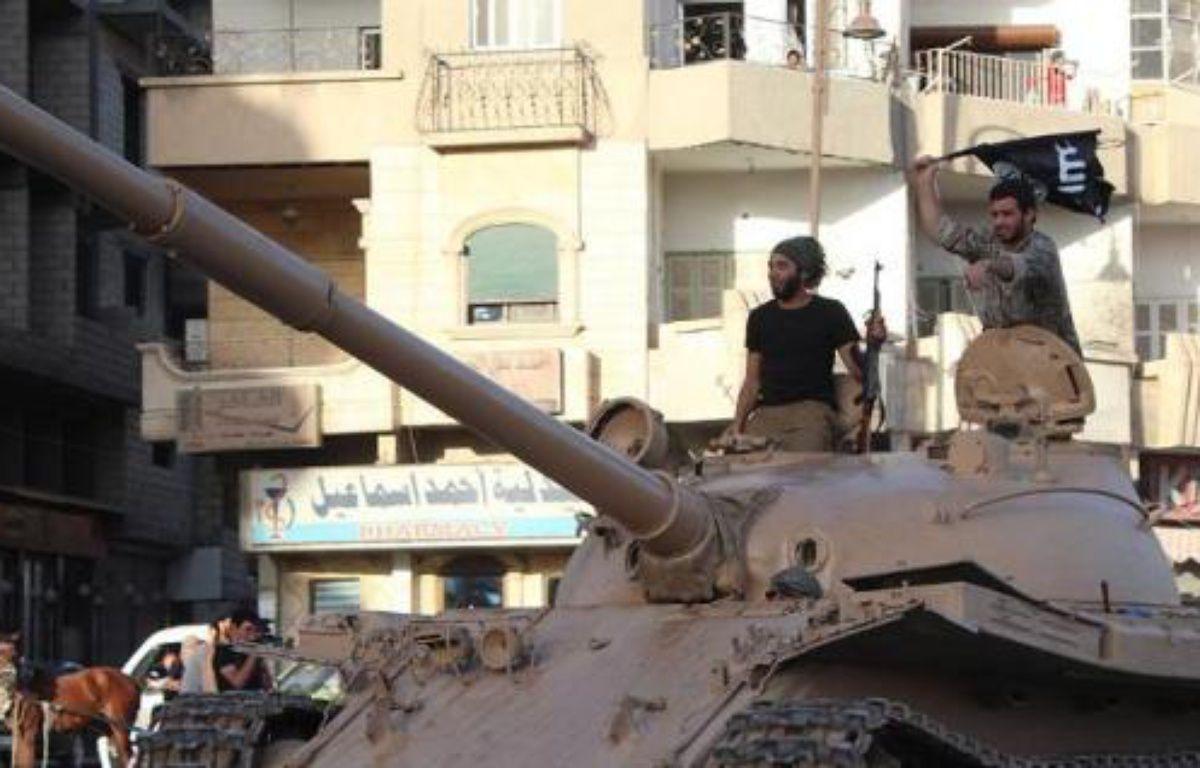 Image fournie par le média jihadiste Welayat Raqa, le 30 juin 2014, montrant des jihadistes de l'Etat islamique sur un char dans une rue de Raqa, en Syrie –  Welayat Raqa
