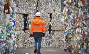 Un employé d'un centre de tri des Côtes-d'Armor marche entre les balles de déchets plastiques en attente d'être recyclés.