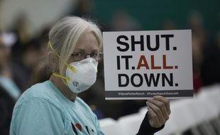 Une femme tient une pancarte pendant un rassemblement  au sujet d'une fuite de gaz massive, à Granada Hills, près de Porter Ranch, en Californie, le 16 janvier 2016