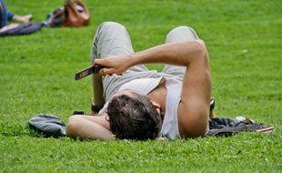 Homme allongé dans un parc lisant ses textos sur son téléphone mobile.
