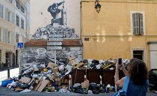 Une femme prend une photo de tas d'ordures, à Marseille.