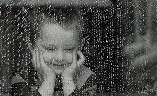 un enfant qui regarde la pluie tomber