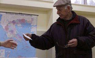 Un électeur tend son bulletin de vote dans un bureau d'Athènes, le 25 janvier 2015.
