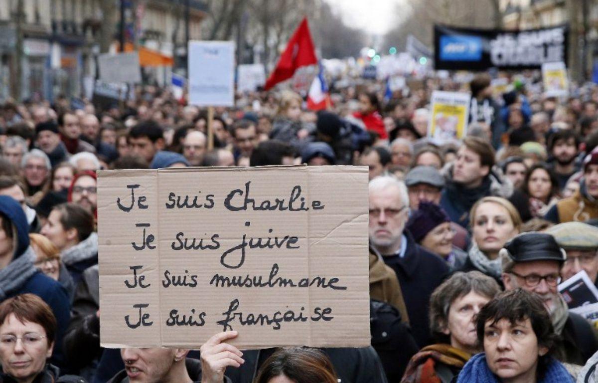 Une manifestante tient une pancarte lors de la marche du 11 janvier 2015, après les attentats de Charlie Hebdo et de l'Hyper Cacher, à Paris. – PATRICK KOVARIK / AFP