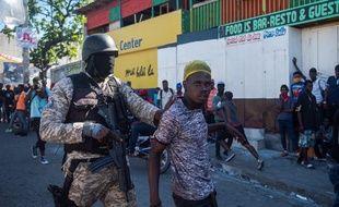 Intervention d'un policier lors d'une manifestation demandant le départ du président Jovenel Moïse, à Port-au-Prince le 7 février 2021.