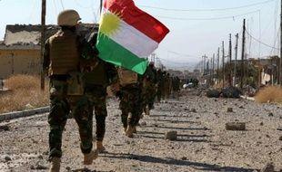 Des combattants kurdes et de la communauté Yazidie entrent avec un drapeau kurde dans la ville de Sinjar, au nord de l'Irak, reprise au groupe de l'Etat islamique (EI), le 13 novembre 2015