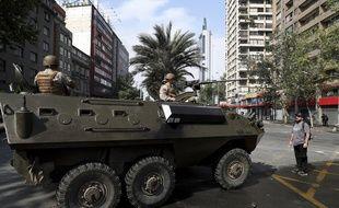 Un manifestant se tient face à un véhicule de l'armée dans les rues de Santiago du Chili, le 19 octobre 2019.