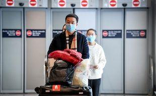 Des passagers en provenance de Chine qui portent un masque à l'aéroport Roissy Charles-de-Gaulle .