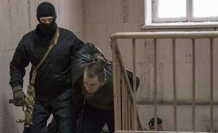 La police russe escorte l'un des cinq suspects dans le meurtre de Boris Nemtsov à Moscou.