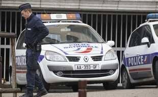 Un policier lors d'une perquisition devant un garage - photo d'illustration
